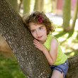 Beautiful blue eyes little girl in the park tree — Stock Photo #5513230