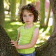 Beautiful blue eyes little girl in the park tree — Stock Photo #5513235