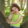 Beautiful little girl eating biscuit over tree — Stock Photo #5513236