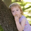 Beautiful little girl eating biscuit over tree — Stock Photo #5513239