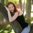 Beautiful woman sitting on the park tree — Stock Photo