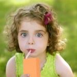 Little girl drinking juice from an orange brik — Stock Photo