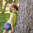 Beautiful little brunette girl beside a tree trunk - Stock Photo