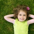 Beautiful little toddler girl happy lying on grass — Stock Photo