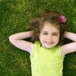 Beautiful little toddler girl happy lying on grass — Stock Photo #5513255