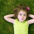 Beautiful little toddler girl happy lying on grass — Stock Photo #5513258