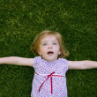 Beautiful little toddler girl happy lying on grass — Stock Photo #5513260
