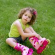 Stock Photo: Little girl sit on the grass with roller skates