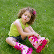 Little girl sit on the grass with roller skates — Stock Photo