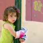 Little girl rolling skate security equipment hug pole — Stock Photo #5513262