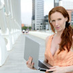 Beautiful redhead woman with laptop — Stock Photo