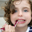 Little girl eating sweet candy with dirty face — Stock Photo