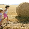 Royalty-Free Stock Photo: Girls playing with the round wheat dried bales