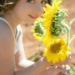 Beautiful little girl in a summer sunflower field — Stock Photo