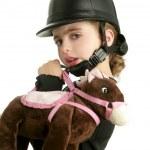 Riding cap little girl hug toy horse — Stock Photo #5513546