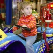 Blond little girl in funfair fairground attraction — Foto Stock