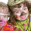 Party little two sisters with painted happy face - Stok fotoğraf