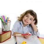 Little girl happy student on desk writing — Stock Photo