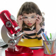 Student little girl with microscope and laptop — Stock Photo