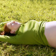 Pregnant woman redhead laying on grass - Stockfoto