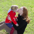 Mother and daugther kissing lips in meadow — Stock Photo