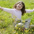 Little girl on garden meadow notebook computer — Stock Photo