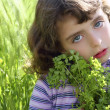Little girl hug green plant meadow spikes — Stock Photo #5513913