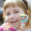 Smiling little girl with lollipop sweet in hand — 图库照片 #5513933