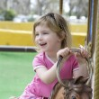 Little blond girl playing horses merry go round — Zdjęcie stockowe #5513936