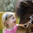 Little blond girl loves her donkey funny portrait - Stock Photo