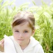 Sad little girl crying outdoor green meadow field - Stockfoto