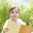 Little blond girl reading book green spikes garden - Stock Photo