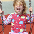 Blond little girl swinging in park swing messy hair — Stock Photo