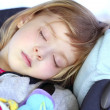 Little girl sleeping on children car safety seat — Stock Photo