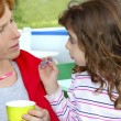 Mother and daughter eating ice cream talking — Stockfoto