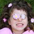 Little girl laying grass daisiy flowers in eyes — Stock Photo #5513993