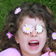 Little girl laying grass daisiy flowers in eyes — Stock Photo