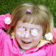 Little girl laying grass daisiy flowers in eyes — Stock Photo #5513995