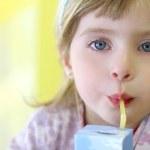 Blond little girl drinking straw tetra brick — Stock Photo