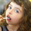 Brunette little girl eating playing plastic spoon — Stock Photo #5514008