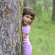 Little girl hide park tree trunk green outdoor — Stock Photo #5514010