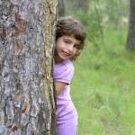 Little girl hide park tree trunk green outdoor — Stock Photo #5514010