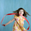 Little girl red ribbon tape dancing over green — Stock Photo