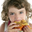 Little girl eating hungry pizza closeup portrait — Stock Photo