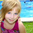 Blond little girl pool garden vacation smiling portrait — Stock Photo #5514107