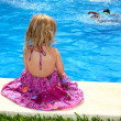 Little blond girl sitting rear back swimming pool — Stock Photo #5514108