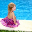 Little blond girl sitting smiling swimming pool — Stock Photo
