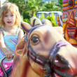 Blond girl with fairground horse enjoy in park — Stock Photo #5514111