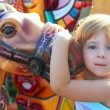 Blond girl with fairground horse enjoy in park — Stock Photo