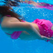 Underwater pink bikini little girl swimming in pool — Stock Photo